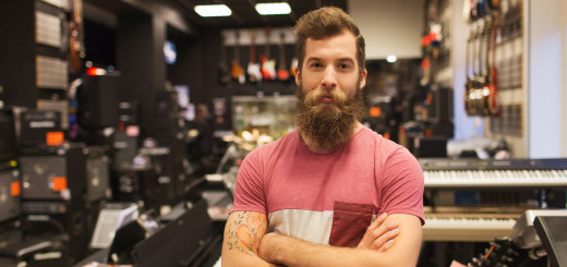 music, sale, people, musical instruments and entertainment concept - male assistant or customer with beard at music store