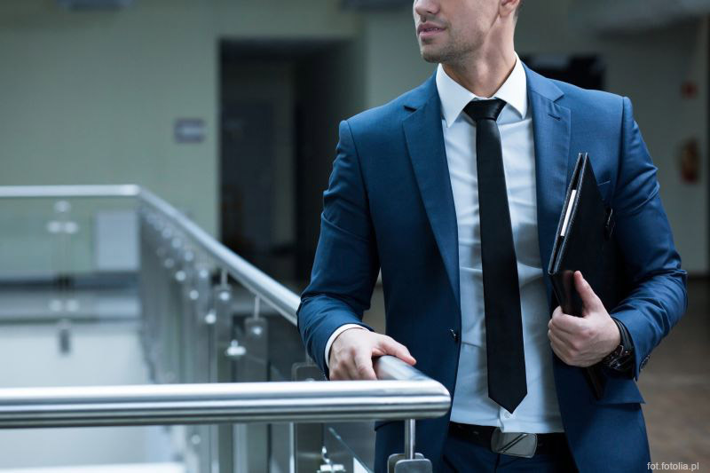 Elegant man leaning against railing in modern, office building, holding folder with documents