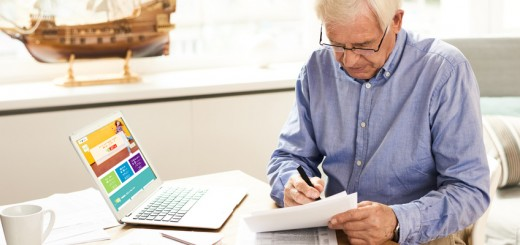 Portrait of modern senior man filling in application papers at home sitting at table with laptop in cozy living room