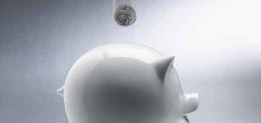 Coin Dropping Into Piggy Bank --- Image by © Royalty-Free/Corbis