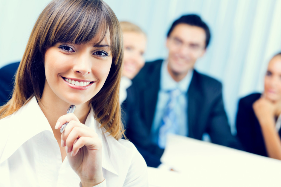 Smiling businesswoman and colleagues on background, at office