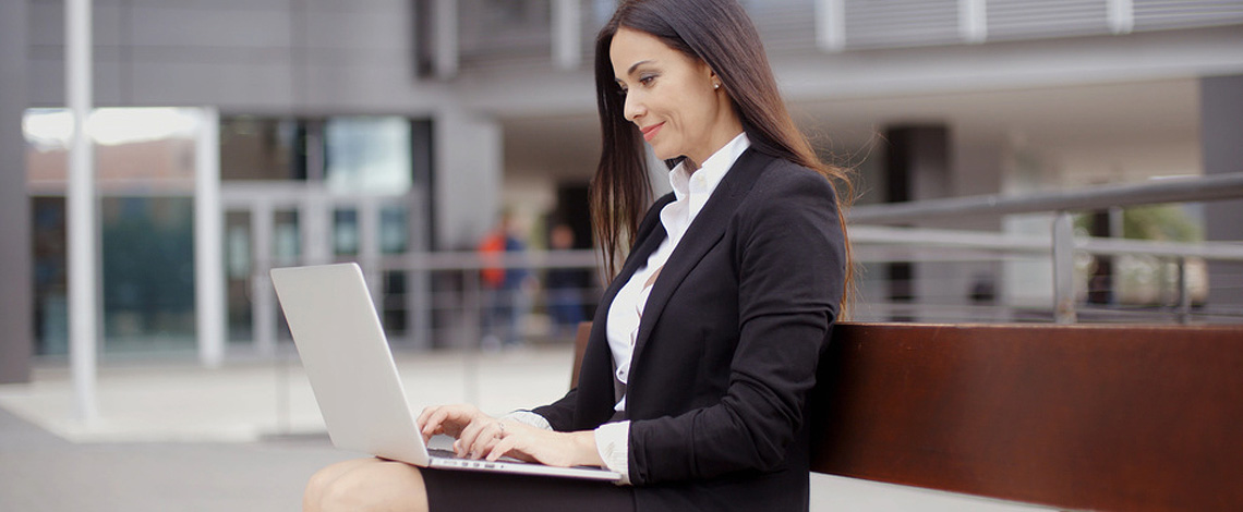 Business woman sitting alone on bench with bag and using laptop computer near office building