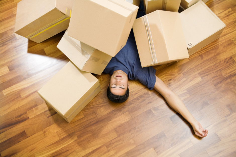 High angle view of young man sleeping underneath moving boxes