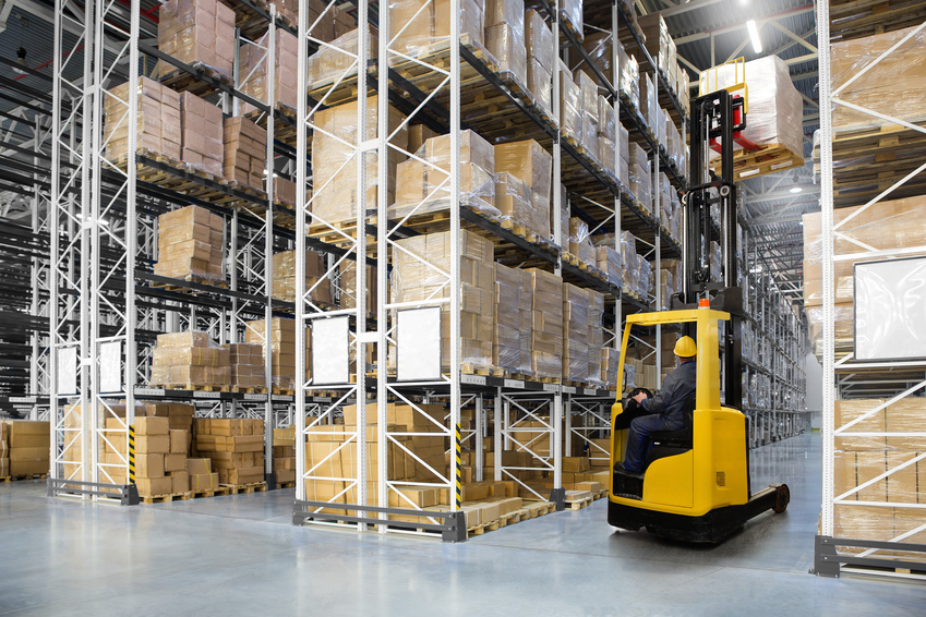 Huge distribution warehouse with high shelves and forklift with operator. Bottom view.