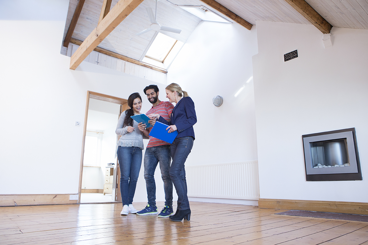 Young Couple being shown a new home by an estate agent holding a clipboard and paperwork. Low viewpoint. They stand looking at a digital tablet together