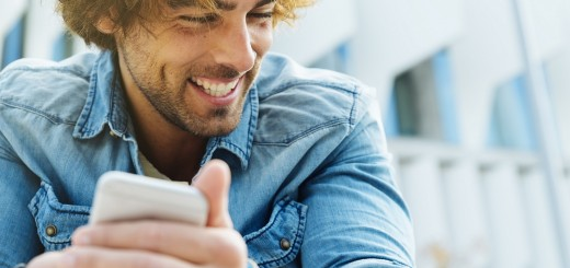 Portrait of Handsome young man smiling when he is using his mobile in the street.